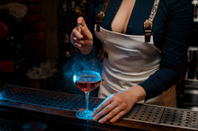 Sexy Woman Barman Spraying Blue-colored Bitter On The Glass