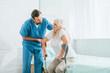 Leinwandbild Motiv male social worker helping sick senior woman with crutches