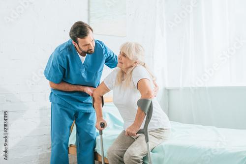 Carta da parati male social worker helping sick senior woman with crutches