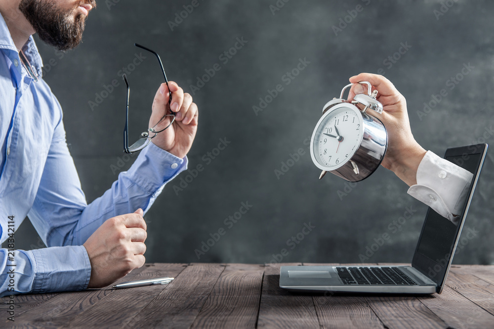 Fototapety, obrazy: Businessman is sitting at the desk and is looking at the hand with clock coming out of the laptop. Metaphor of spending time at work