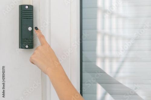 Fotografia, Obraz A woman's hand presses the doorphone button.