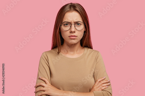Foto  Displeased sullen female has discontent expression, keeps hands crossed, shows her dislike, frowns face, feels unhappy, has staight dark hair, poses against pink background