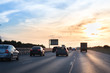 Cars on busy road driving in evening sunset. highway with metal safety rail or barrier
