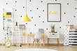 Leinwanddruck Bild - Small wooden desk and a modern chair for a young pupil and creative, vibrant yellow decorations in a scandinavian style child bedroom interior with white walls