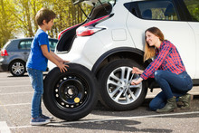 Little Boy Helping His Mother To Change Flat Tyre