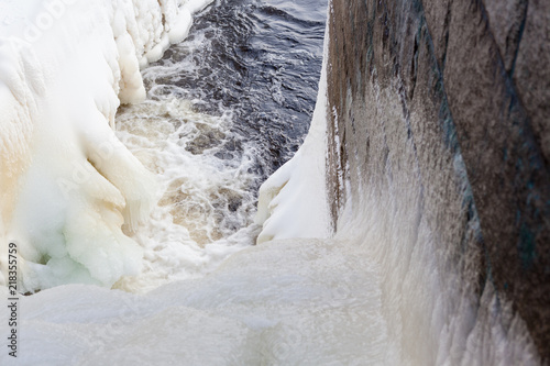 Deurstickers Dam Dam at winter flowing water and ice formations