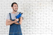 Young Asian man holding power drill standing in front of white brick wall, smiling and looking at camera on a white brick wall background. , concept for home DIY