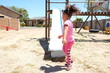 Little girl playing on playground slide