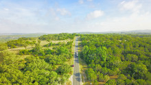 Top View Scenic Winding Country Road Through Green Farmland In Hill Country. Aerial Rural Road Though Countryside Of Texas Ranch, Blue Sky