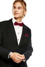 A Handsome Young Man In A Blazer And Button Up Shirt, Accessorized With A Burgundy Red Pinstripe Bow Tie And Matching Pocket Square. The Blond Looking Aside Over The White Background, Hands Clasped.