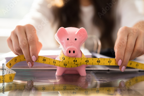 Fotografie, Obraz  Businesswoman Measuring Piggybank With Measuring Tape