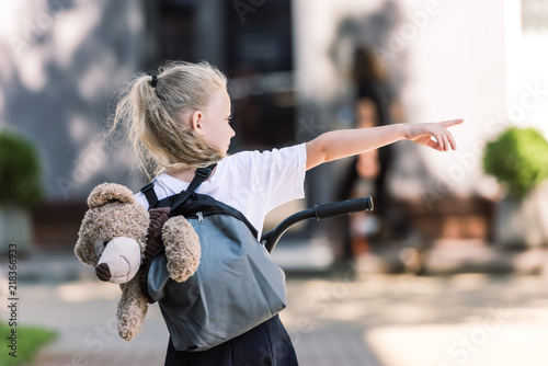 back view of adorable little schoolgirl with backpack and teddy bear riding scooter and pointing away with finger on street