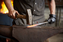 An Artisan Metal Worker In Ear Protectors Using A Hammer To Shape A Red Hot Piece Of Metal On An Anvil.