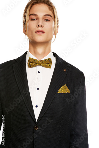 1e99cfbd88 A young man in a black suit jacket and button up shirt, accessorized with an  olive green bow tie and pocket square. The blond guy with a ponytail  looking at ...