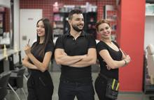 Equipo De Atractivos Peluqueros Posa Para Foto De Stock Dentro De Una Peluquería Uniformados De Negro.