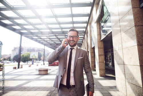 Smiling young businessman walking with confidence to a new business meeting Fototapete