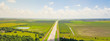 Panorama aerial horizontal view of Interstate 10 highway near rest area with exit and service road. Scenic road surrounded by green oak trees under cloud blue sky in USA. Transportation background