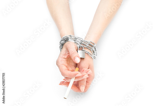 Fotografia  Woman's hands tied by chain with cigarette on white.