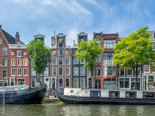 Photo  Amsterdam canal, bridge and typical houses, boats and bicycles during the day, Holland, Netherlands
