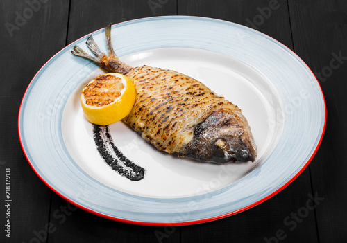 Fotografie, Obraz  Grilled dorado fish with lemon and truffle sauce on plate on wooden background