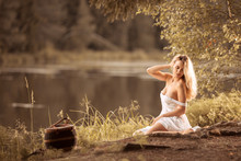 Sensual Young Woman Sitting Relaxing By The Lake In Sexy White Shirt  At Sunset
