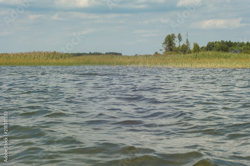 Fotografía  Lake on a sunny day with ripples on the surface of the water, blue sky and white clouds