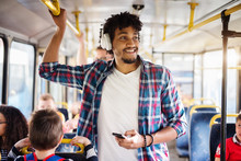 Young Afro-American Man With Headset On His Head Is Looking Away While Riding In A Bus.