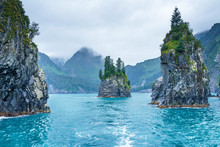 Blue Waters And Tree Covered Rocks Jutting Out Of Water On A Cloudy Morning At Porcupine Bay At Kenai Fjords National Park, Alaska