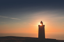 Silhouette Of A Lighthouse With Lens Flare And Sand Dunes In Sunset Light. Rubjerg Knude Lighthouse, Lønstrup In North Jutland In Denmark, Skagerrak, North Sea