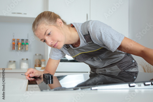 Fototapeta Woman installing hob in kitchen obraz