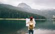 Leinwanddruck Bild - Travel woman with backpack checks map