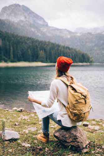 Fotografia  Woman traveler with backpack checks map