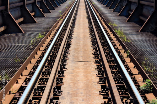 Photo  Strong old rusted metal railroad bridge with hard supports, metal grids with gre