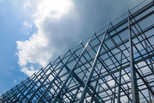 A Large Building Of Steel Structure In The Sky With Sun And Clouds.