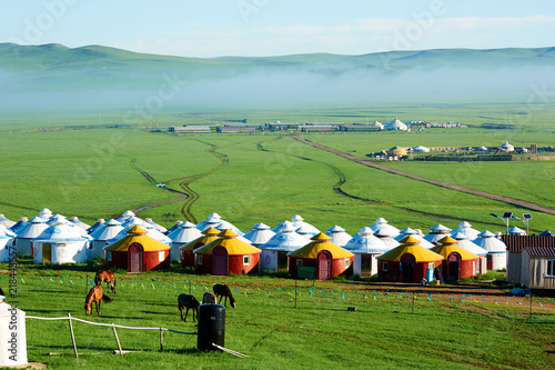 The mongolian yurts in summer grassland sunrise.