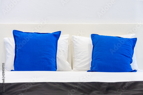 Fototapety, obrazy: Two white pillows and blue cushions on bed in a bedroom. The plain design of romantic light pale room.