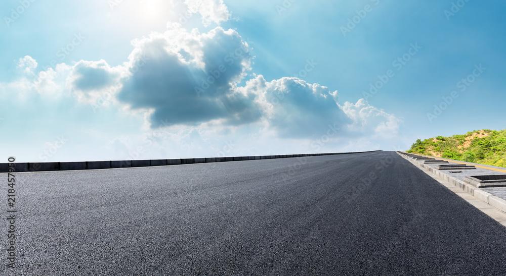 Fototapeta Empty asphalt road and mountain scenery under the blue sky
