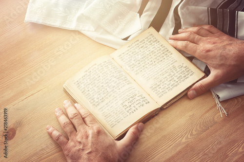 Jewish man hands holding a Prayer book, praying, next to tallit. Jewish traditional symbols. Rosh hashanah (jewish New Year holiday), Shabbat and Yom kippur concept.