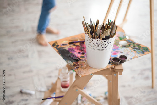 Artistic equipment: easel, paint brushes, tubes of paint, palette and paintings on work table in a artist studio Canvas Print
