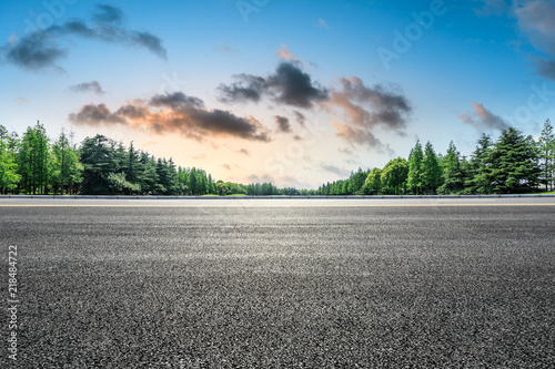 Photo  Empty asphalt road and green forest landscape at sunrise