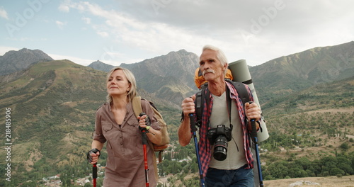 Fotografía  Active senior caucasian couple hiking in mountains with backpacks, enjoying thei
