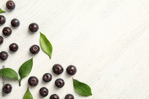 Photo Flat lay composition with fresh acai berries and leaves on wooden background