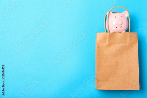 Flat lay composition with shopping bag and piggy bank on color background Canvas Print
