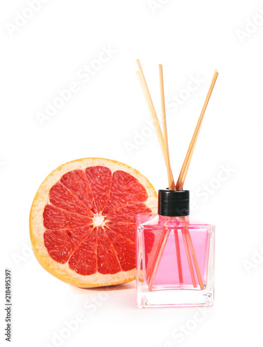 Aromatic reed air freshener and grapefruit on white background
