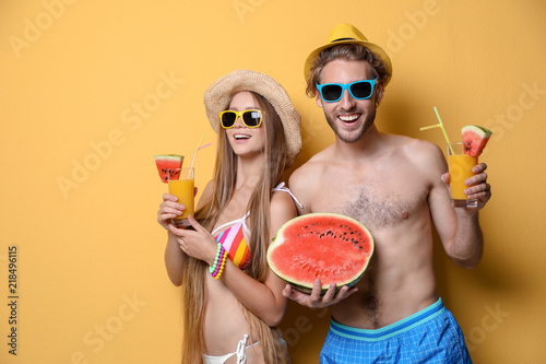 Young couple in beachwear with cocktails on color background