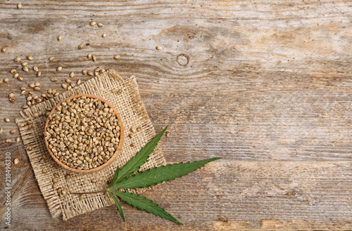 Obraz Bowl of hemp seeds and space for text on wooden background, top view - fototapety do salonu