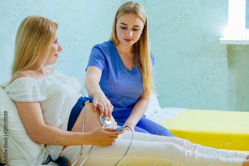 Blond young midwife examination belly of pretty blond pregnant woman with CTG scanning in practice Wallpaper Mural