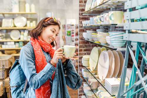 Photo  Asian girl shopping for kitchenware in retail store