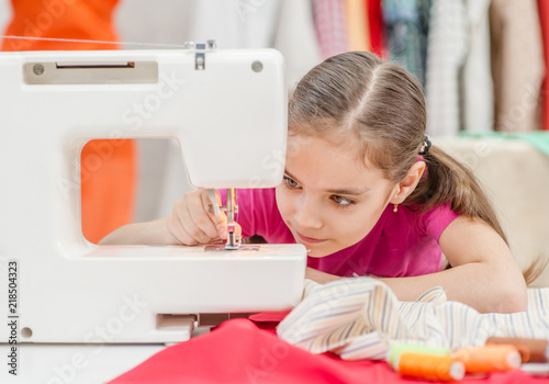 Fotografia, Obraz Little girl prepares a sewing machine for work, inserts a thread