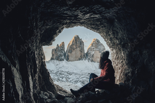 Poster Antilope Silhouette of young woman sitting inside cave shaped heart symbol while enjoy mountain view.